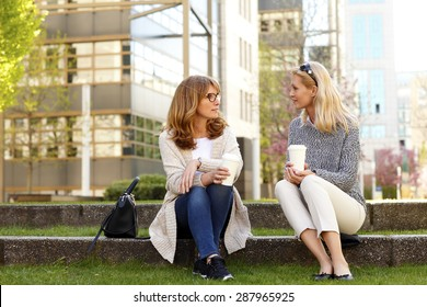 Portrait of two middle age women sitting at office park while on coffee break. Businesswomen relaxing while drinking coffee and chatting with each other.