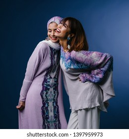 Portrait of two Middle Eastern Muslim women in festive ethnic Raya clothing posing in a studio. They are both young, attractive and beautiful. The women are friends or relatives.