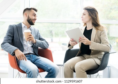 Portrait of two modern business people, man and woman, sitting in designer chairs and talking to each other in sunlit room