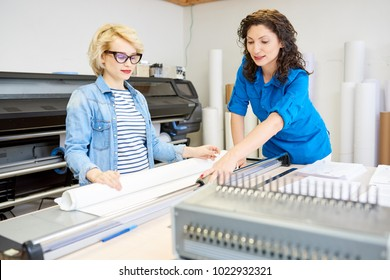 Portrait of two modern  women working in printing shop or publishing company, loading machines with paper and cutting brochures