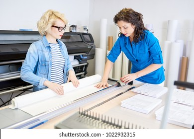 Portrait of two modern young women working in printing shop or publishing company, loading machines with paper and cutting brochures