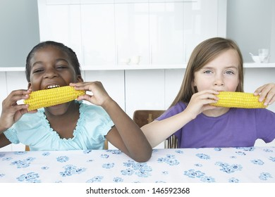 Portrait of two multiethnic girls eating corn cobs at table