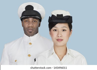 Portrait of two multi-ethnic US Navy officers over light blue background