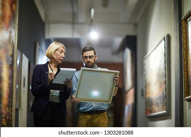 Portrait of two museum workers inspecting paintings standing in art gallery, copy space