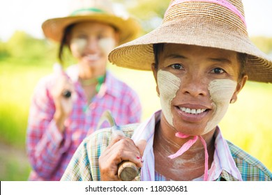 Portrait of a two Myanmar farmer with thanaka powdered face who works in the field