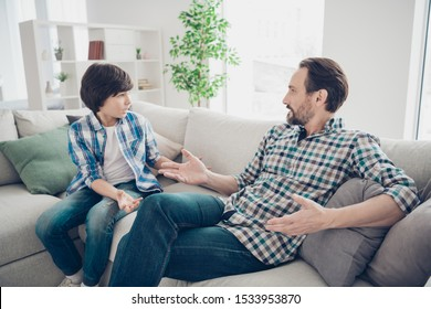 Portrait of two nice attractive friendly guys dad and pre-teen son sitting on couch discussing psychology generation problems in light white modern style interior living-room