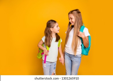 Portrait of two nice attractive lovely cheerful cheery pre-teen girls with colorful backpacks holding hands gossiping talking isolated over bright vivid shine yellow background