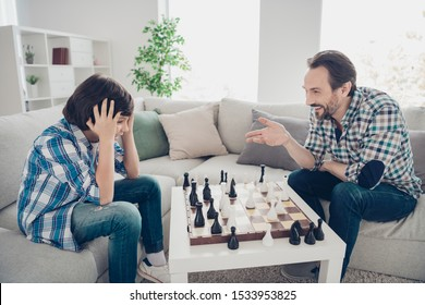 Portrait of two nice cheerful cheery glad guys dad and pre-teen son sitting on sofa playing chess son loses game in light white modern interior house living-room indoors