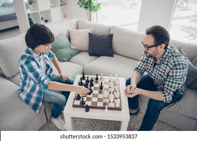 Portrait of two nice intelligent focused concentrated serious guys dad and pre-teen son sitting on sofa playing chess moving pieces in light white modern interior house living-room