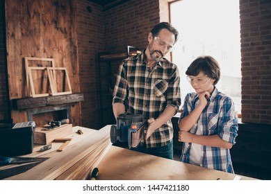 Portrait of two nice person concentrated cheerful woodworkers master artisan handyman dad daddy teaching son interesting old-fashioned profession at modern loft industrial brick interior