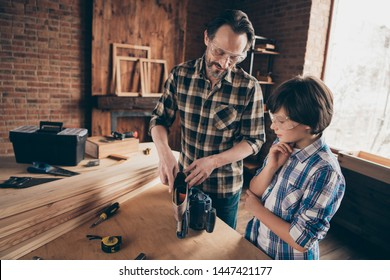 Portrait of two nice person focused cheerful woodworkers master handyman dad daddy teaching son industry interesting profession at modern loft industrial brick interior