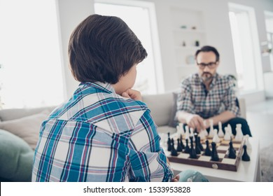 Portrait of two nice skilled focused concentrated serious guys dad and pre-teen son sitting on sofa playing chess moving pieces in light white modern interior house living-room