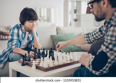 Portrait of two nice skilled focused serious guys dad and pre-teen son sitting on sofa playing chess moving pieces thinking strategy in light white modern interior house living-room