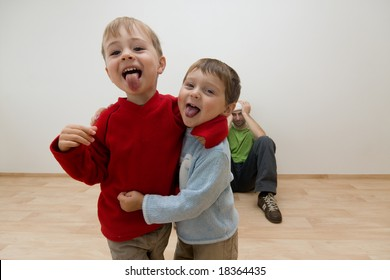 Portrait of two noisy children being naughty, with adult in background sat on floor covering his ears.