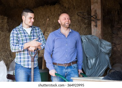 Portrait of two ordinary smiling male farmers with working tools in barn. Selective focus