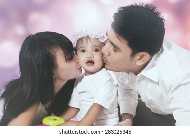 Portrait of two parents kissing their baby together, shot against a light glitter background
