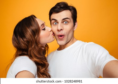Portrait of two people making selfie while woman kissing her boyfriend in cheek over yellow background