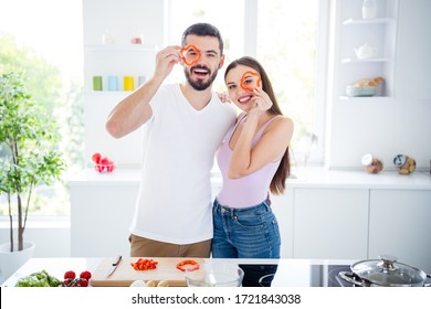 Portrait of two people positive vegans spouses hold pepper watch enjoy prepare tasty dish lunch man woman hug embrace in kitchen house indoors