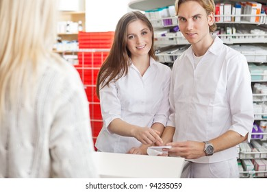 Portrait of two pharmacists at counter with customer