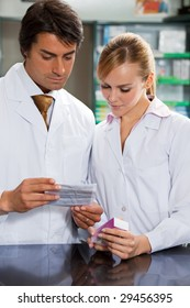 portrait of two pharmacists reading directions of medicine