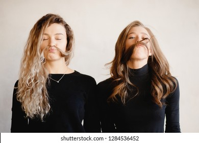 Portrait two of playful kinky woman sisterhood with eyes closed in black clothing putting lock hair on her face like mustache