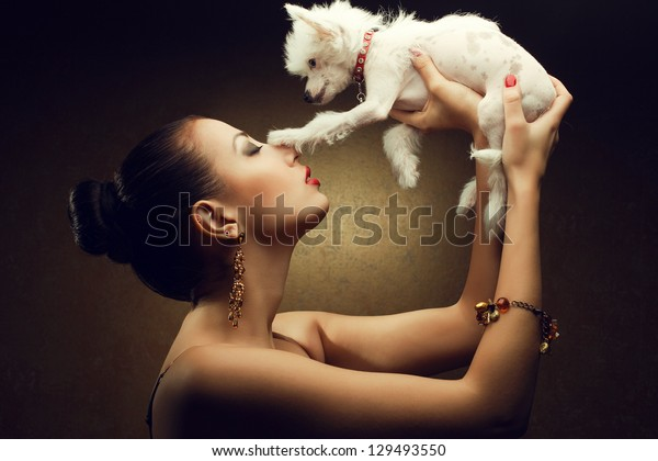 Portrait of two playing friends:  fashionable model with sexy red lips holding her white little chinese crested dog. Both posing over golden background. Studio shot
