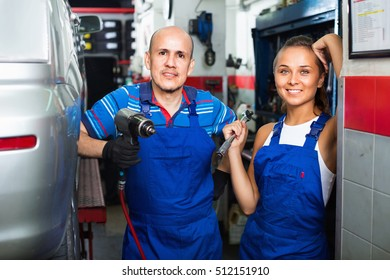 Portrait of two  positive glad workers in protective overalls in auto workshop