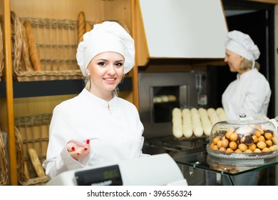 Portrait of two positive smiling female bakers in bakery