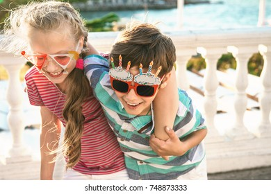 Portrait of two preteen children - boy and girl (9-10 years old) dressed in funny party glasses having fun and birthday celebrations.