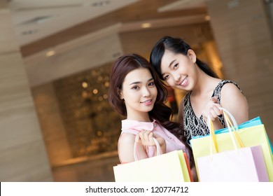 Portrait of two pretty girls with shopping bags