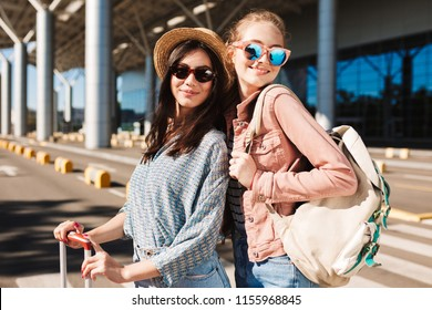 Portrait of two pretty smiling girls in sunglasses happily looking in camera with backpack on shoulder and airport on background