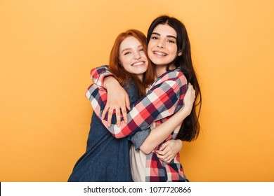 Portrait of two pretty young teenage girls hugging and looking at camera isolated over yellow background
