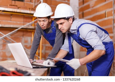 Portrait of two professional builders using laptop for reading plan of building