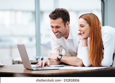Portrait of two professionals looking at a laptop screen