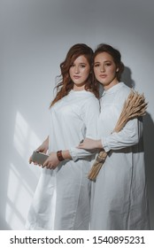 Portrait of two red-haired ethnic twin girls with a smartphone and a sheaf of wheat, as a symbol of the connection between the past and the present.