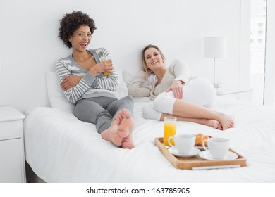 Portrait of two relaxed smiling young female friends with breakfast tray in bed at home