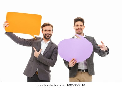 Portrait of a two satisfied business men holding empty speech bubbles isolated over white background