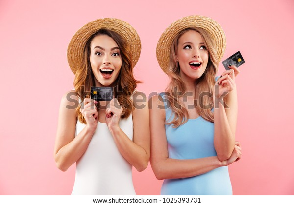 Portrait of a two satisfied girls dressed in swimsuits and summer hats holding credit cards isolated over pink background