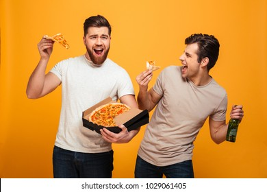 Portrait of a two satisfied young men watching football while drinking beer and eating pizza isolated over yellow background