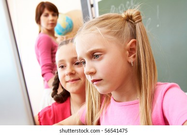 Portrait of two schoolgirls looking at the laptop during lesson with teacher on background