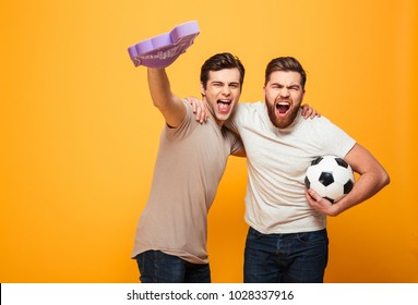 Portrait of a two screaming young men holding soccer ball and foam glove isolated over yellow background