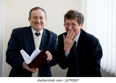 Portrait of a two senior businessmen reading the book