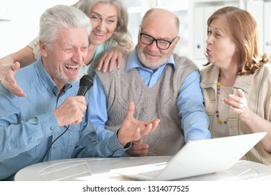 Portrait of two senior couples reading newspaper