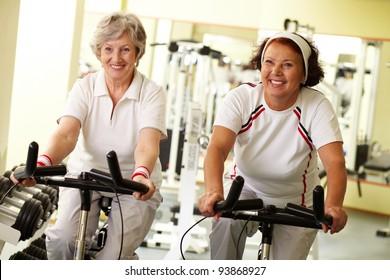 Portrait of two senior women on simulators in fitness club