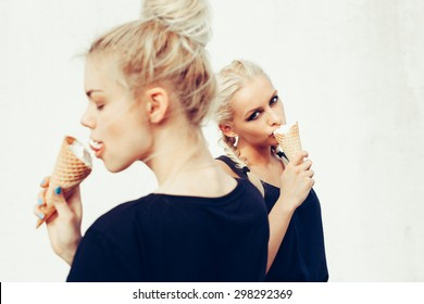 Portrait of two sensuality young beautiful girls eating sweet ice-cream. Outdoors lifestyle
