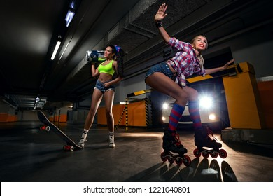 Portrait of two sexy friendly girls with boom box with cassette tape going to make party on roller skates and skate in modern car parking .