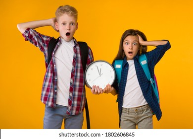 Portrait of two shocked schoolchildren holding clock, grabbing their heads isolated over yellow studio wall