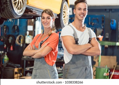 Portrait of two skilled auto mechanics looking at camera with confidence while wearing gray overall in a modern automobile repair shop with experienced employees