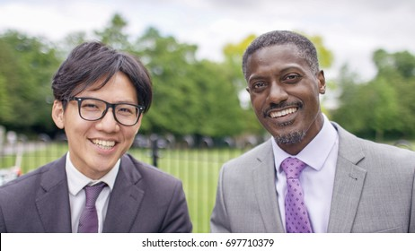 Portrait of two smiling business men looking to camera during a video call