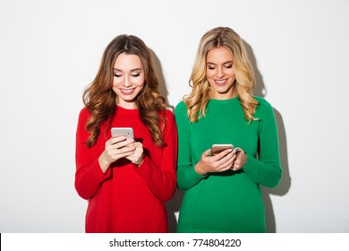 Portrait of two smiling girls dressed in sweaters using mobile phones isolated over white background